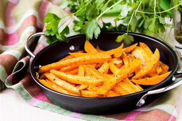 Sweet potatoes, batata, sliced, fried in pan with spices, herb