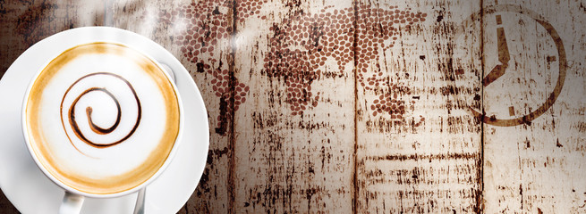 Coffee cup and saucer on vintage wood background