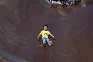 Niño deslizándose por tobogán gigante
