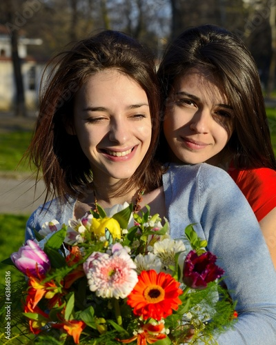 Two beautiful young women hugging and holding bouquet