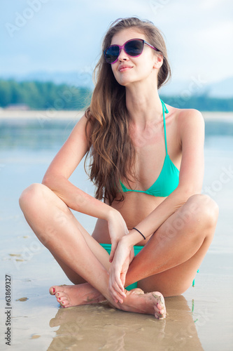 Young woman in sunglasses sitting on beach in the evening