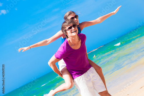 Happy couple in sunglasses on holiday piggybacking cheerful on