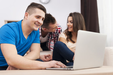 Smiling man using laptop with friends at home