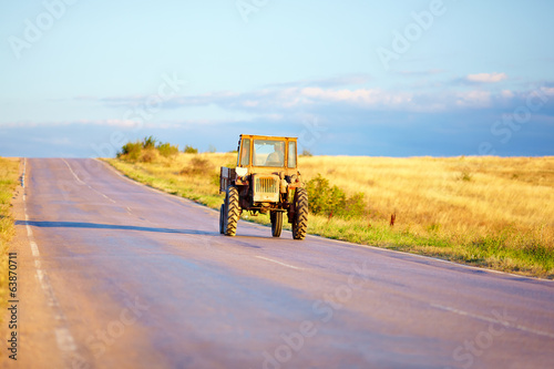 farmer drives tractor on country road