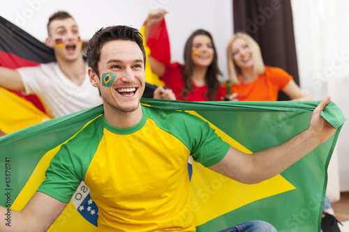 Brazilian man with friends enjoying the soccer on TV