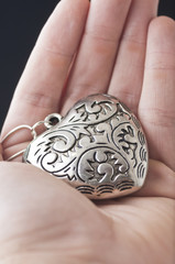 hand holding heart shaped pendant