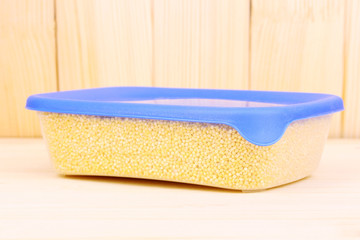 Filled plastic container on wooden background