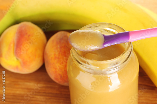 Jar with fruit baby food, spoon and fruits