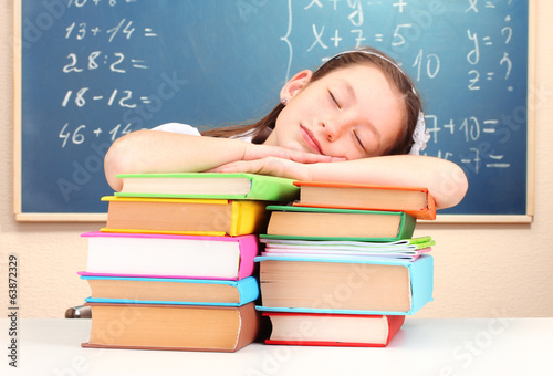 little schoolgirl sleep in classroom near blackboard