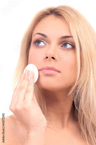 Beautiful young woman with a cotton pad