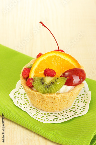 sweet cake with fruits on wooden table