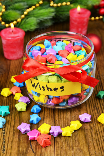 Paper stars with dreams in jar on table close-up