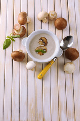 Mushroom soup in white pot on wooden background