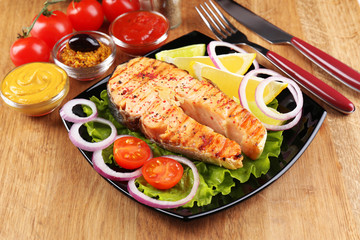 Tasty grilled salmon with lemon and vegetables, on wooden table