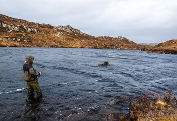 Man fishing for trout and salmon in a  Scottish loch