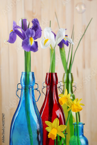 Beautiful irises and daffodils in bottles, on wooden background