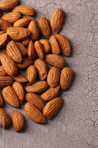 Almonds on color wooden background