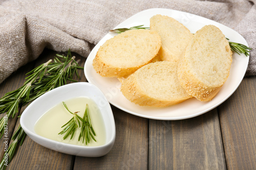 Fresh bread with olive oil and rosemary on wooden table