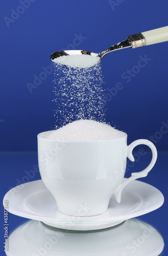 Sugar in cup on blue background