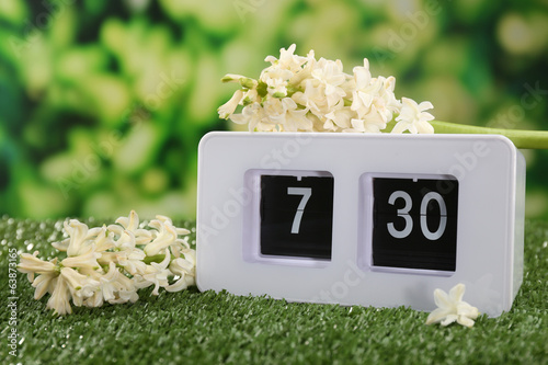 Digital alarm clock on green grass, on nature background