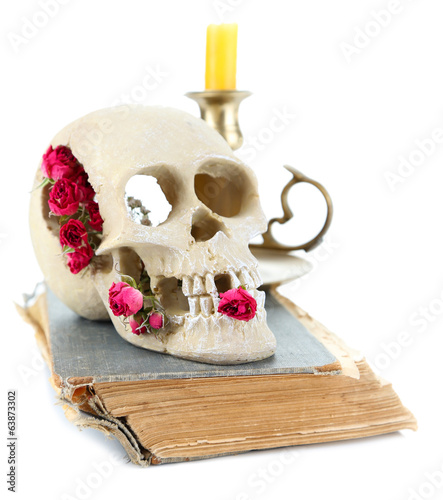 Skull with dried roses on old book and candle isolated on white