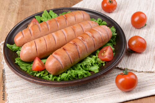 Grilled sausage on plate on table close-up