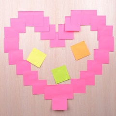 Heart made of adhesive note close-up