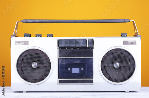 Retro cassette stereo recorder on table on yellow background