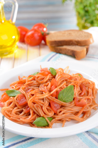 Pasta with tomato sauce on plate on table on light background