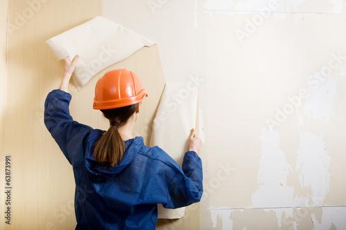 worker removes old wallpaper