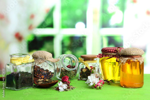 Assortment of herbs and tea and honey in glass jars