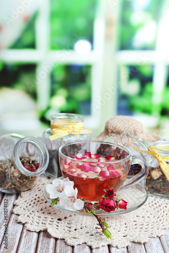 Assortment of herbs,  tea in glass jars and hot drink in cup