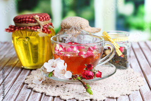 Assortment of herbs,tea and honey in glass jars and cup of hot