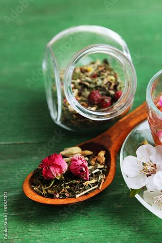 Assortment of herbs, tea in glass jars and cup of hot drink