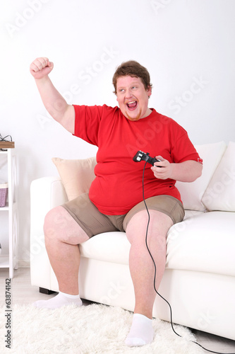 Fat man playing video games on home interior background