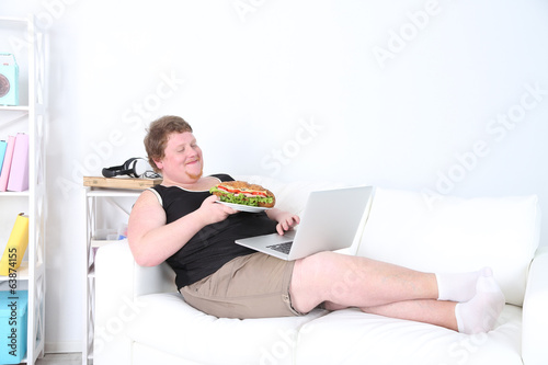Fat man sitting with laptop