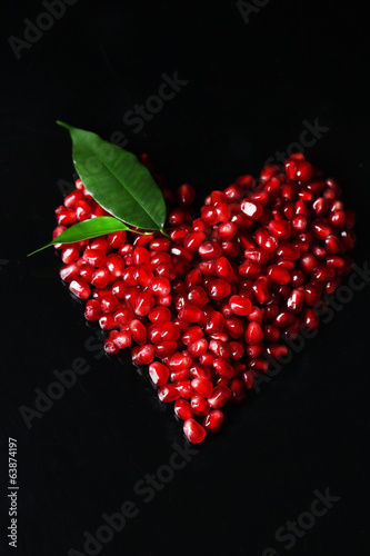 Heart made of seeds of pomegranate isolated on black
