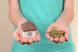 Little house-toy and coins in woman hands close-up