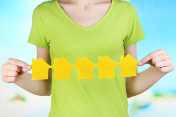 Woman hold houses on natural background