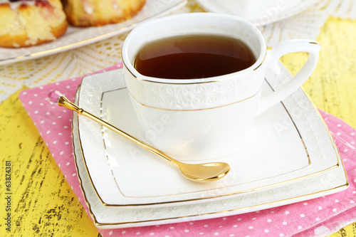 Cup of tea with sweet pastries on table close-up