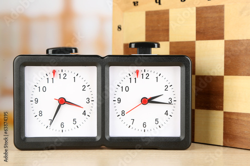 Chess clock and board on light background
