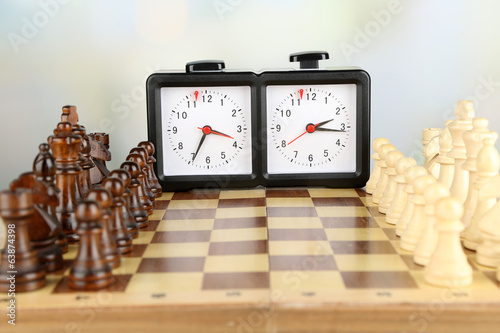 Chessboard with chess and clock on light background