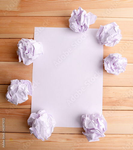 Sheet of white paper with crumpled  paper  and pencil