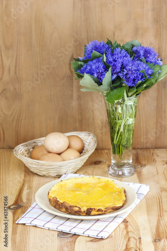 Omelet on wooden table. Basket with eggs and bouquet of cornflow