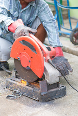 Sparks flying metal cutting abrasive disk by worker