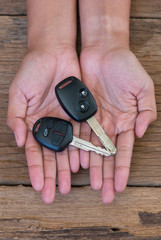 Hand with a car keys on wood background
