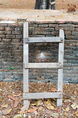 Small diagonal wooden ladder on the dirty brick wall