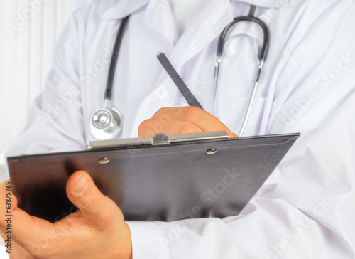 Unrecognizable physician with clipboard