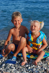 The girl of 3 years, the blonde, and her elder brother on a sea