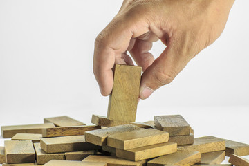 Hand picking up wood domino